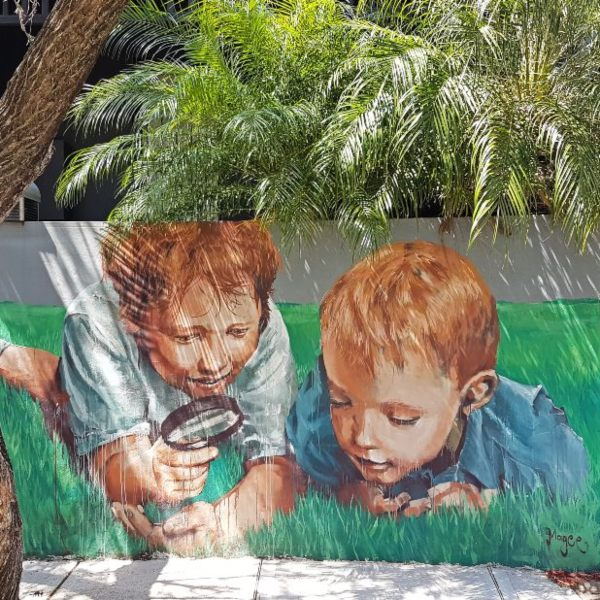 Mural of Two boys with magnifying glass in Enmore Sydney Australia by Street Artist Fintan Magee